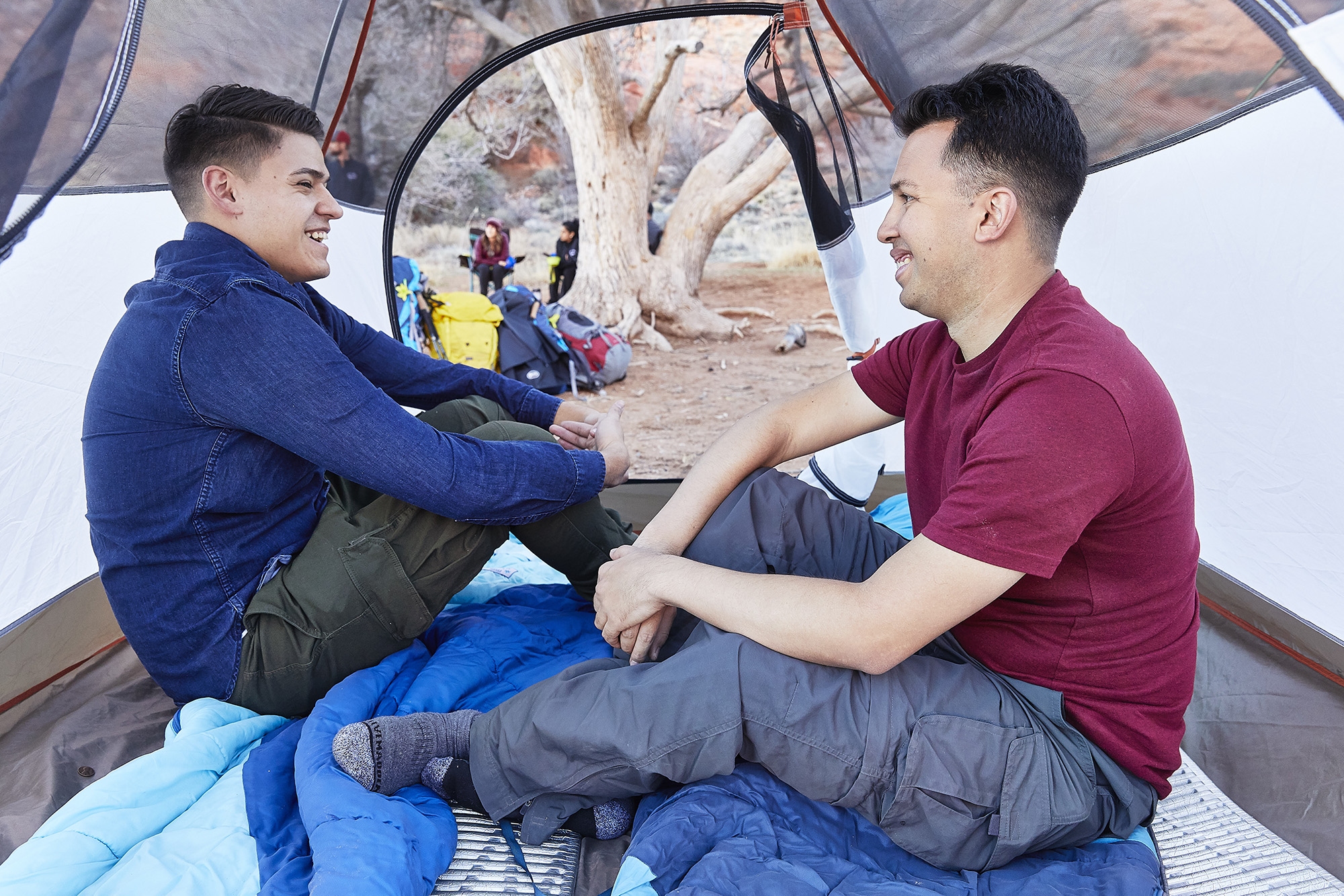 Two men sitting in a tent.