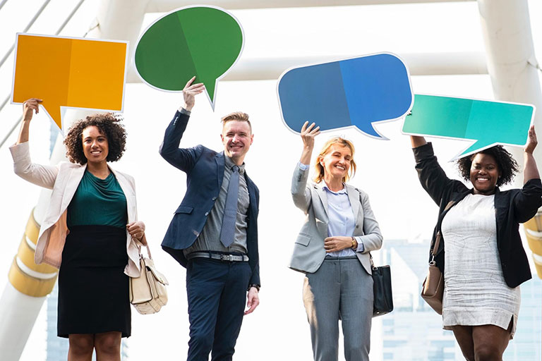 Four people holding speech bubbles signs