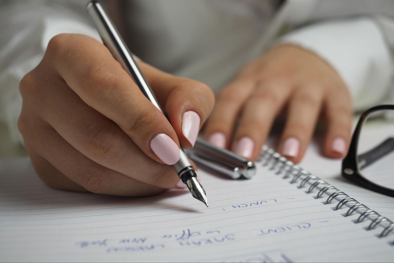 A woman writing a list on paper