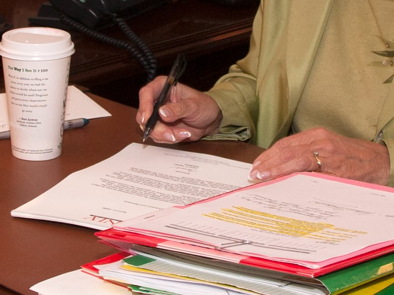 A faculty member reviewing files and notes from a organized folder.