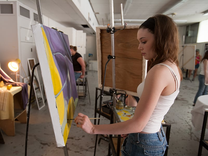Female student painting on a canvas