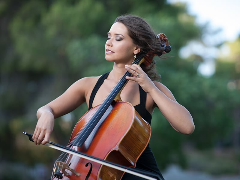 Woman passionately playing a large stringed instrument in an outdoor setting