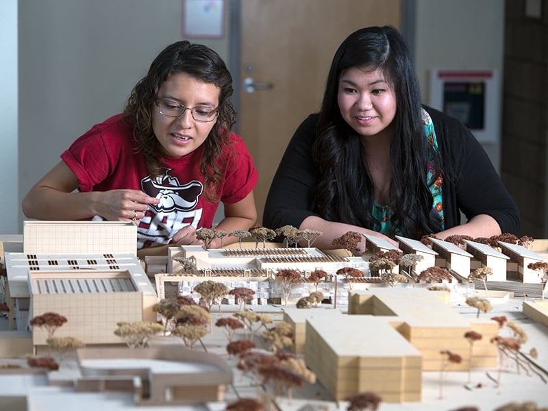Two female students building a large model of a cluster of buildings