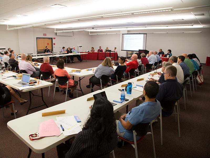 A large curriculum committee meeting with faculty members around the room.