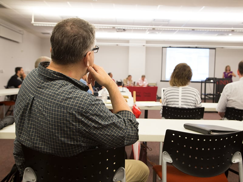 A faculty senate member reviewing information presented by a projector.