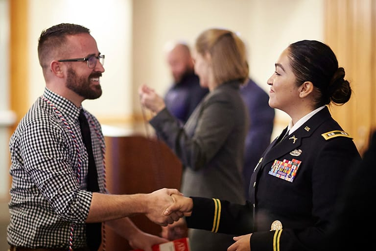 Young man shaking the hand of a young woman wearing a military formal uniform