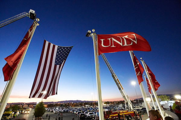 Large American Flag displayed outside Sam Boyd Stadium along side red U.N.L.V flags.