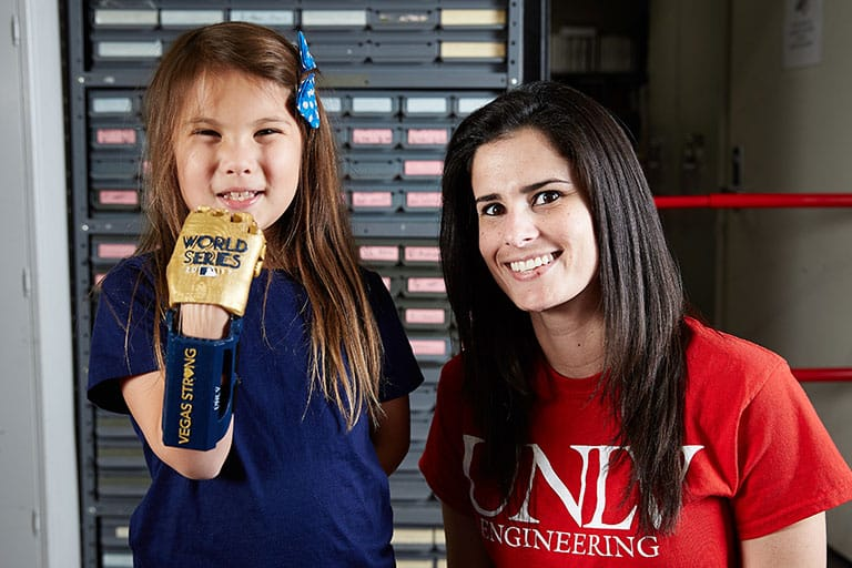 Hailey poses with Maria Gerardi, UNLV engineering graduate student behind 7-year-old Hailey Dawson's World Series pitch using a 3D-printed prosthetic hand.