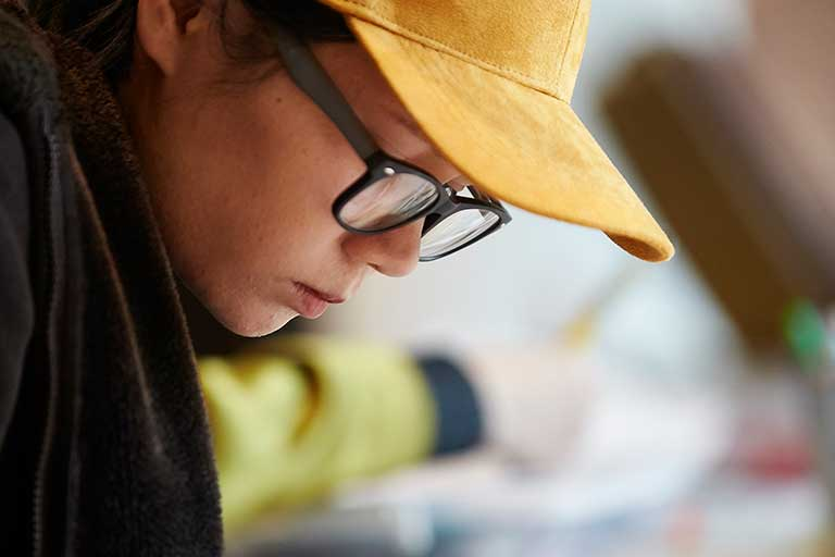 Student with yellow cap focuses intently on their drawing