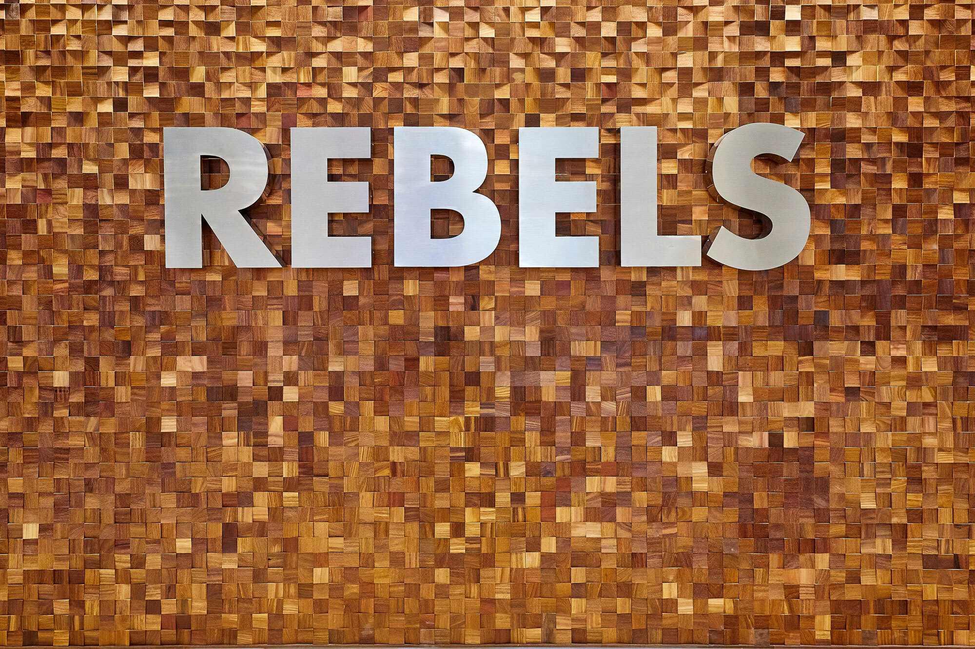 Silver letters spelling Rebels on a gold wall