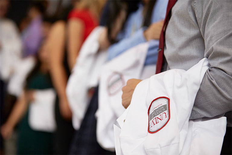 Students taking their oath and receiving their first white coat and stethoscope in the White Coat Ceremony