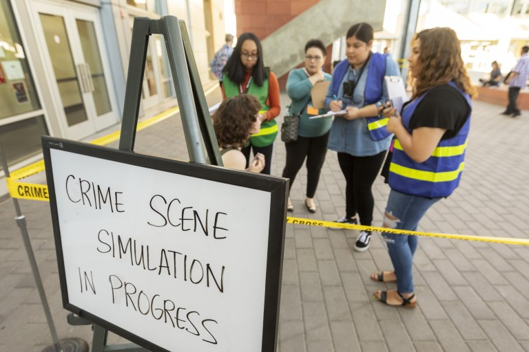 Crime Scene Simulation in Progress sign with people standing behind