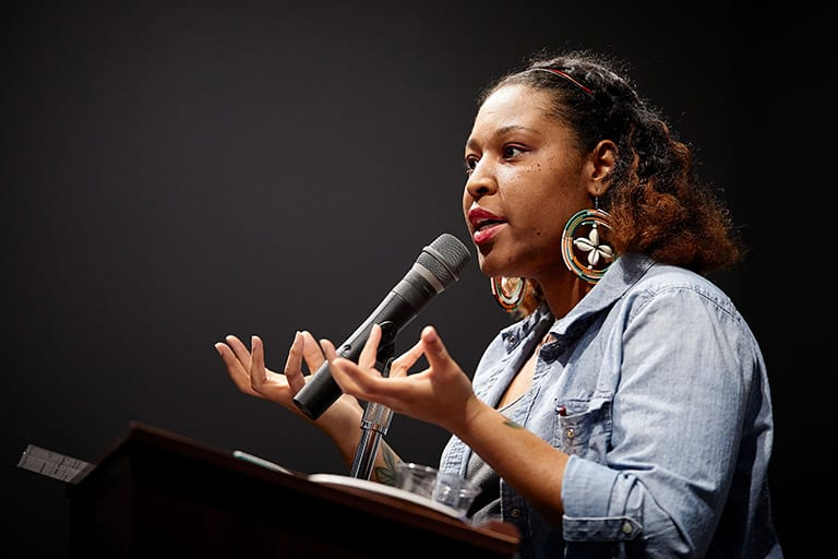 Young, black woman speaking into a microphone on a podium.