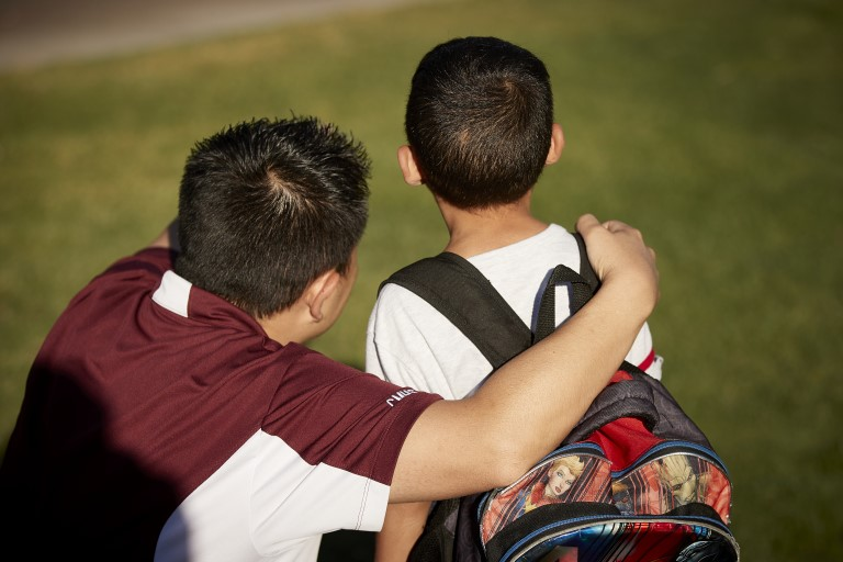 Man with arm around kid with backpack