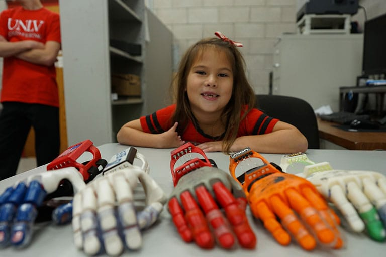 Hailey sits at table with multiple robotic hands