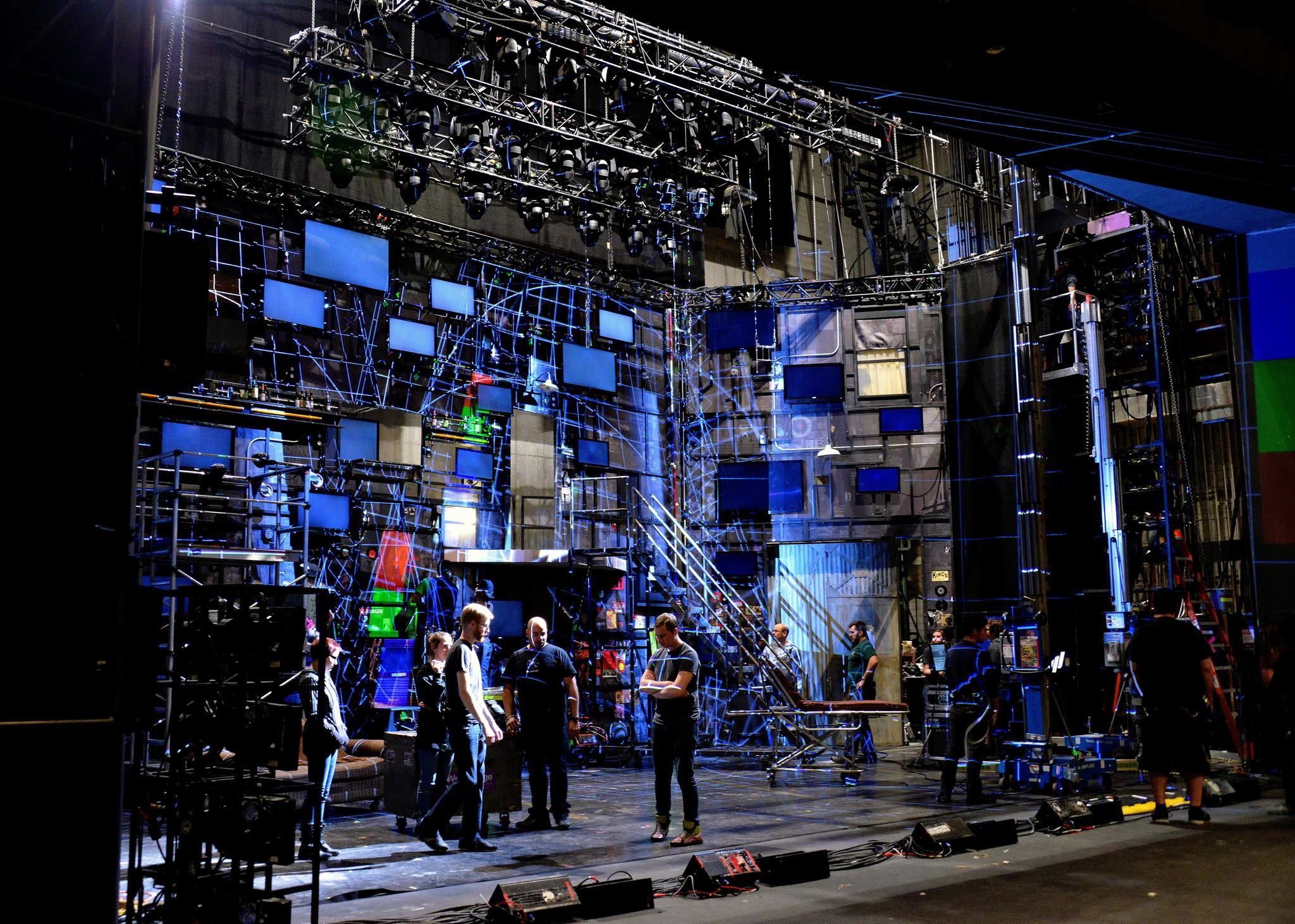 A group of stagehands stand at the center of a stage decorated with several large, blue screens surrounding them