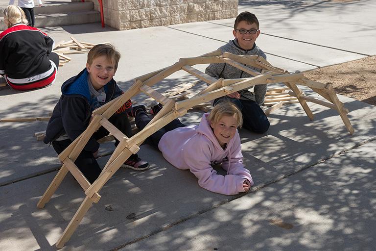 Three children surrounding a wooden bridge.
