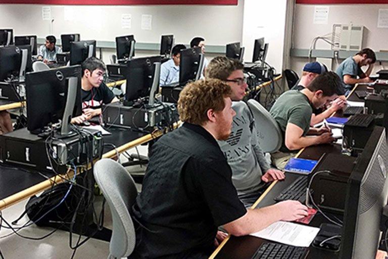 Men gathered around a computer.