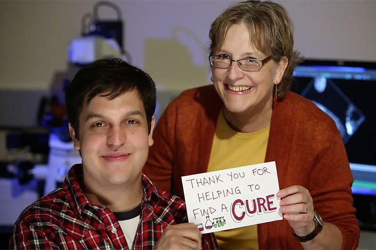 "A man and woman smiling while holding a sign that says ""Thank you for helping to find a cure."""
