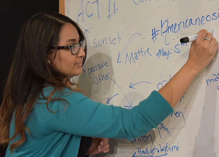 A woman writing on a whiteboard with a marker.