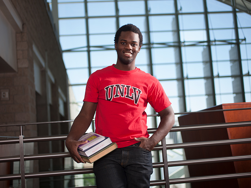 Student wearing a UNLV shirt and holding books