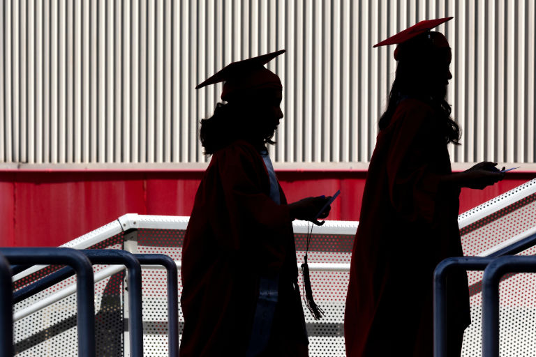 Two students walk with diploma in hand