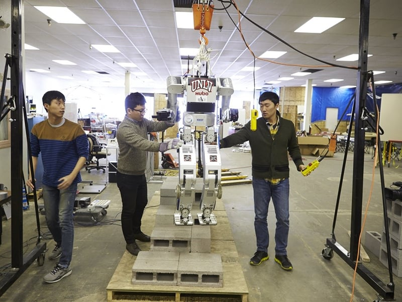 Three male students constructing a robot