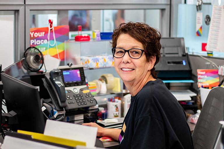 A staff member sitting a desk