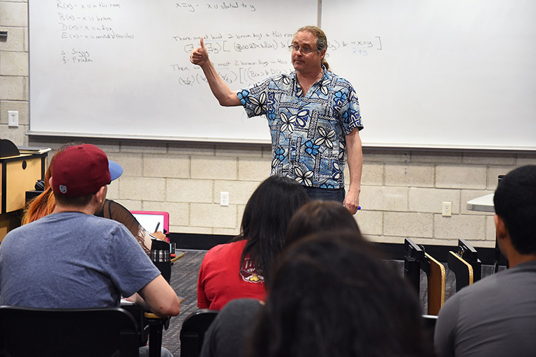 A professor teaching in a classroom.