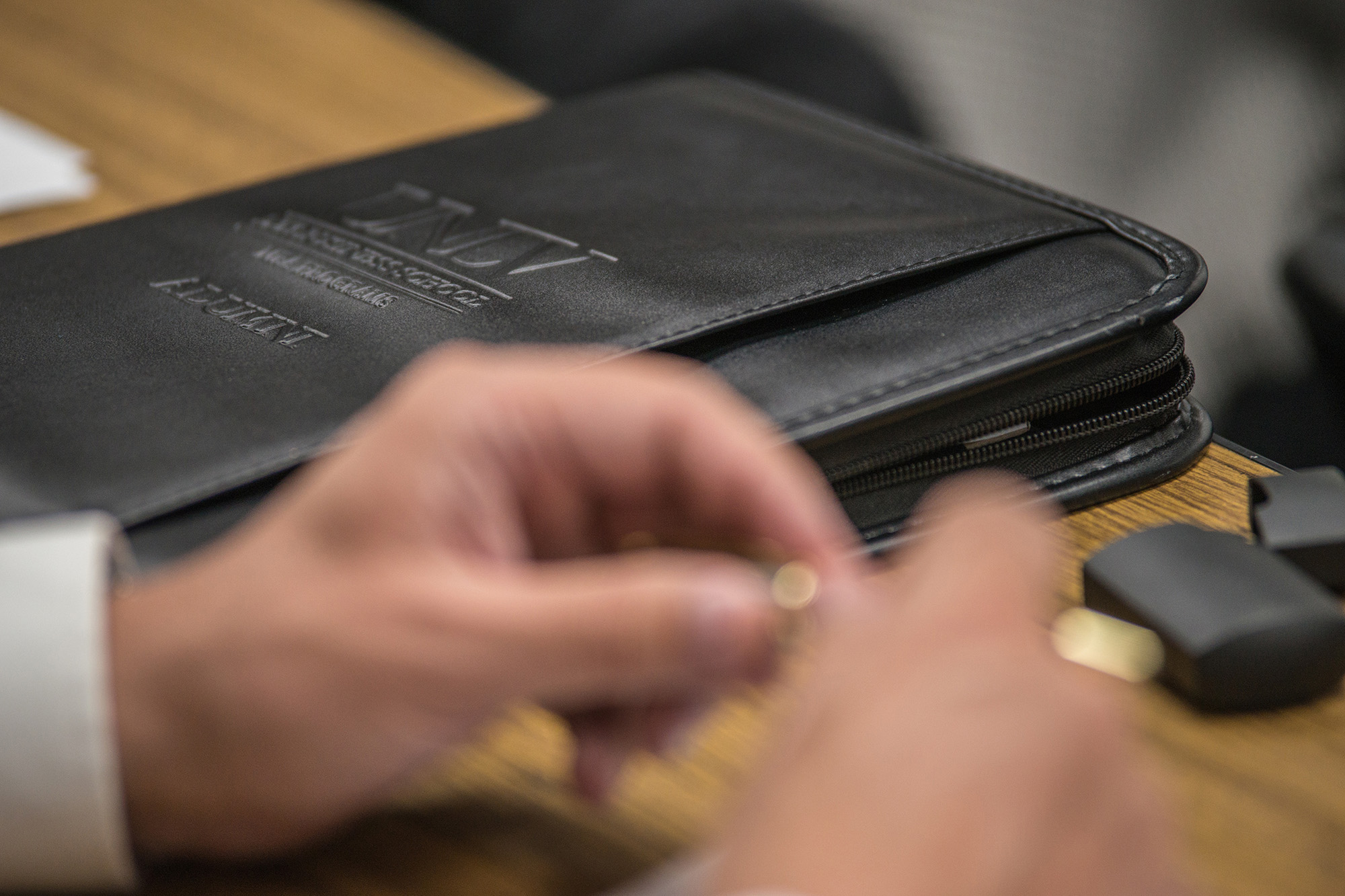 A closeup shot of a man's hands and a black briefcase