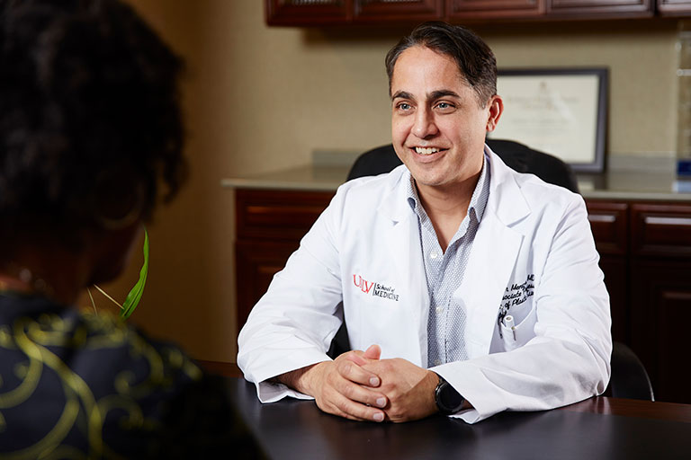 John Menezes, M.D., Associate Professor of Plastic Surgery, talking to a patient