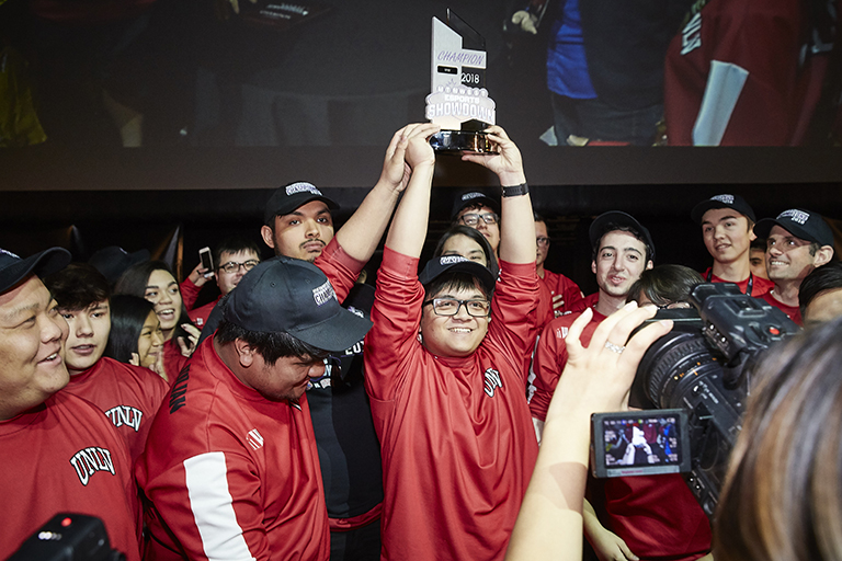 U-N-L-V esports team holding a trophy above their heads