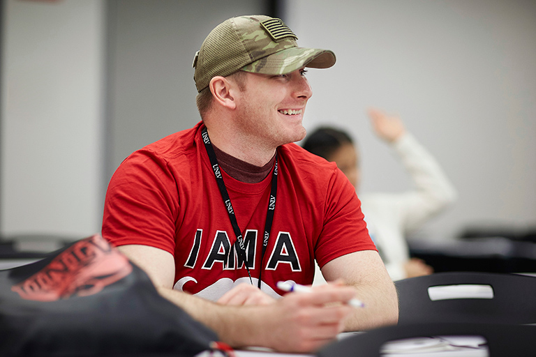 "A man wearing a camouflage cap and a red shirt with ""I am a rebel"" on it."