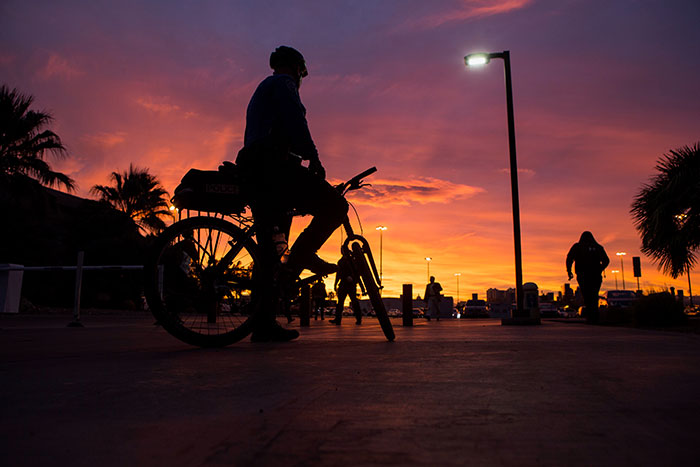 Policeman on bike during sunset