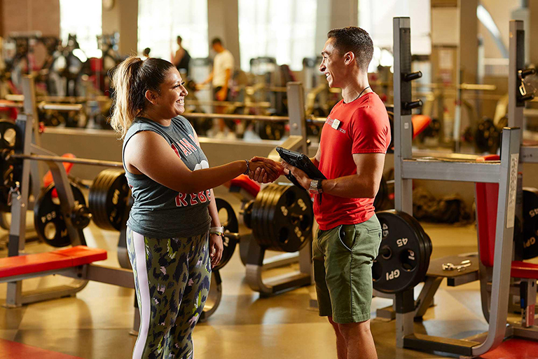 Personal trainer shakes hands with client.