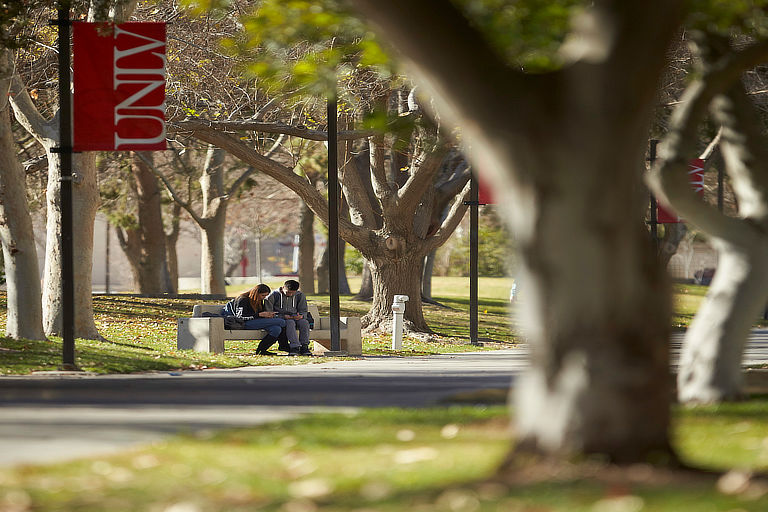 Wide shot of two students sitting on a bench that is located underneath the UNLV flag