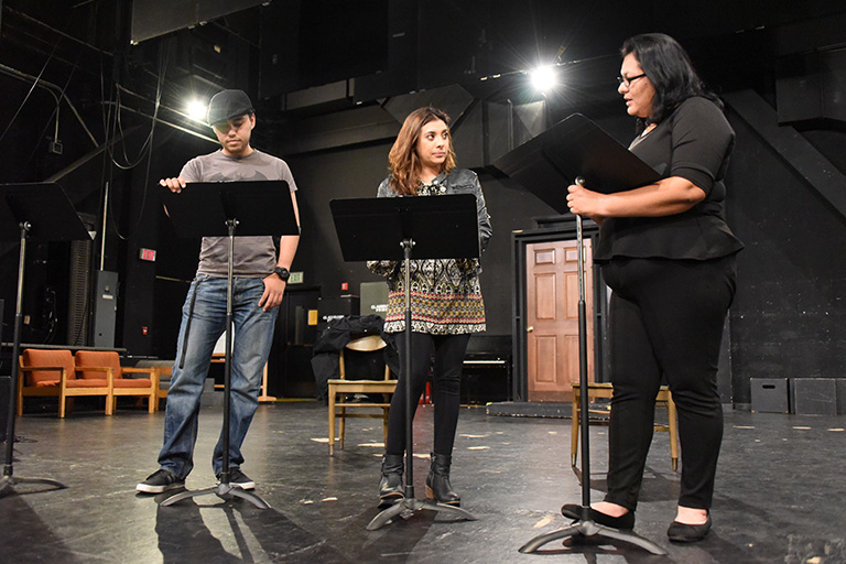 Three students standing on a stage