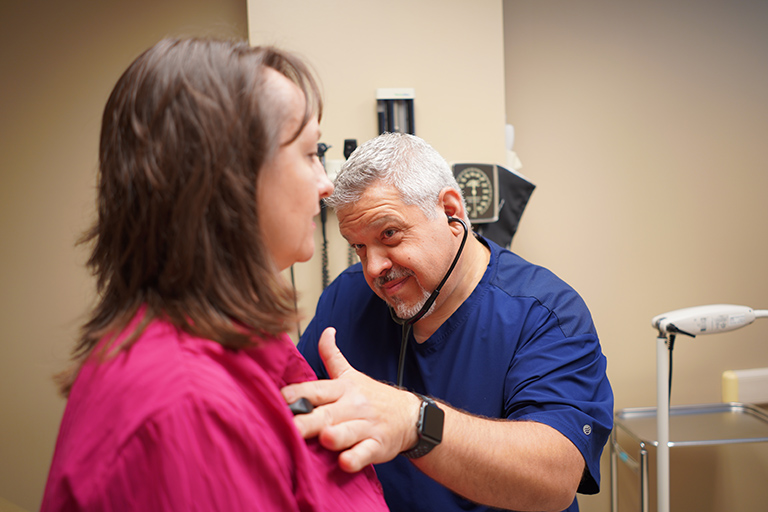 A faculty member at an appointment being seen by a doctor.