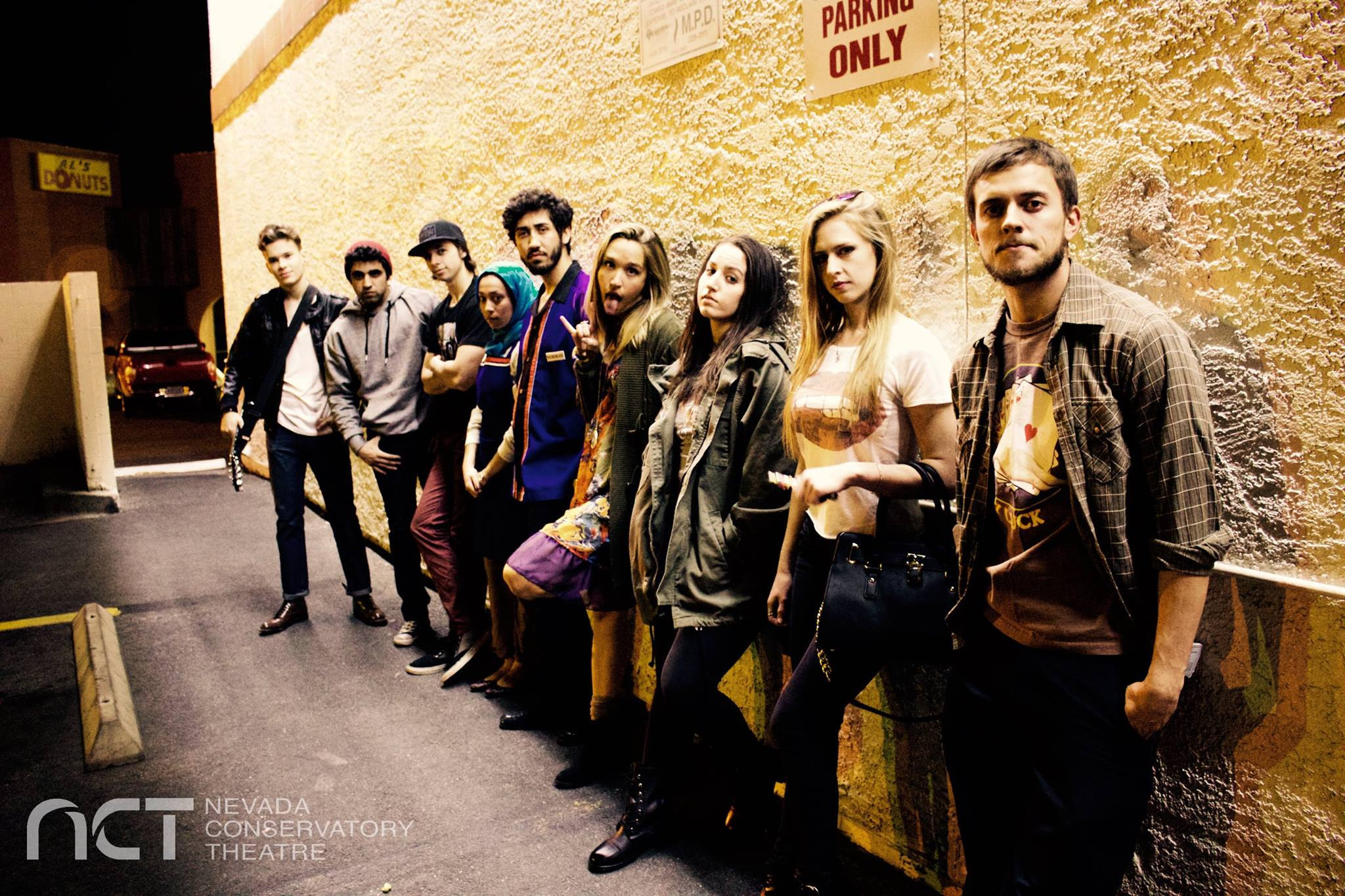 Group of rebellious-looking students leaning against a beige wall onstage