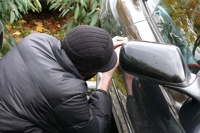Person dressed in black trying to break into a car