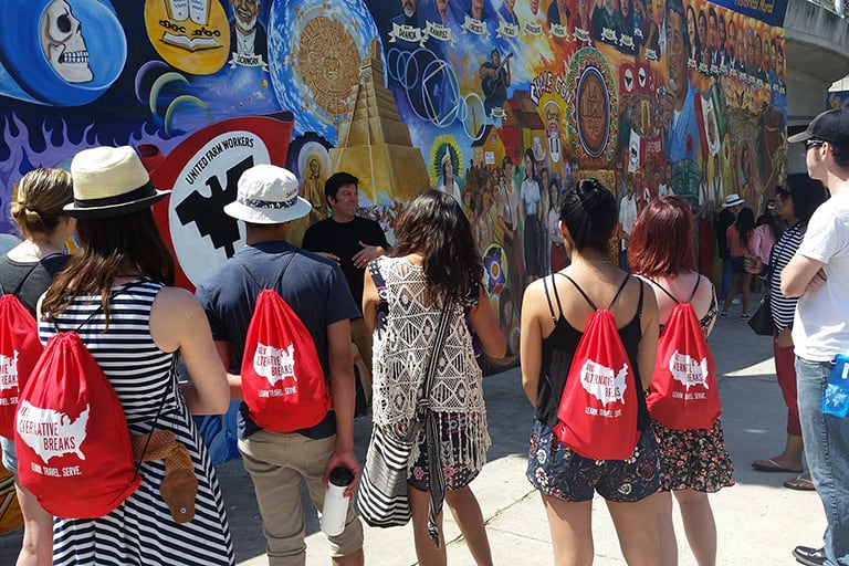 A group of student wearing alternative breaks backpacks looking at a mural