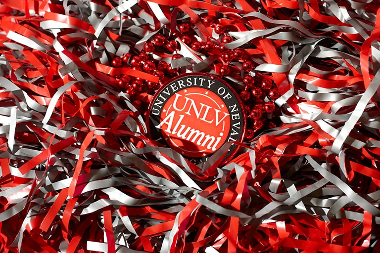 A UNLV Alumni badge surrounded by red and gray confetti