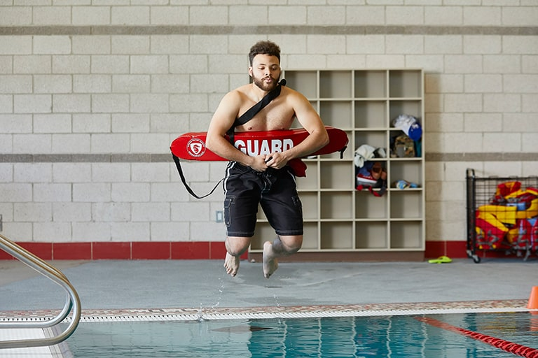 Life guard jumping feet first into water
