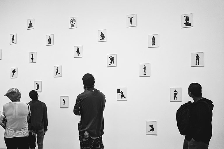 Black and white of a group of four people looking at numerous polaroid-sized images hanging on a wall