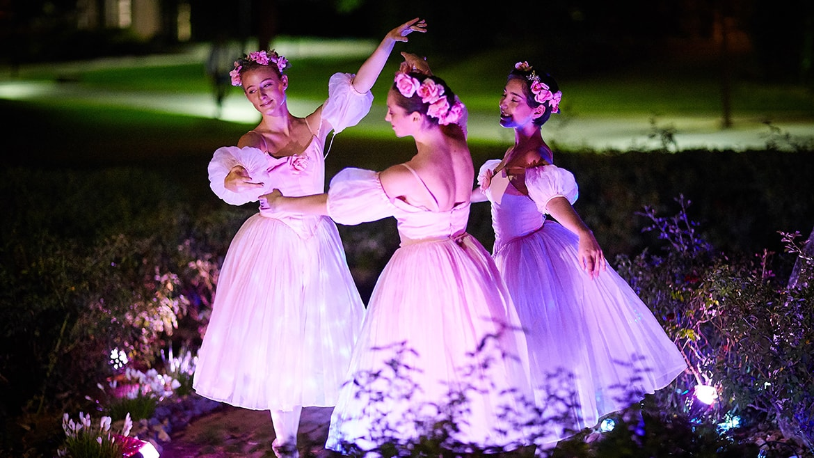 Three ballerinas dancing in garden at night