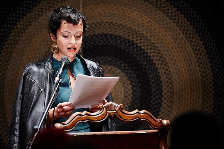 Susana Ferreira reads from paper at podium