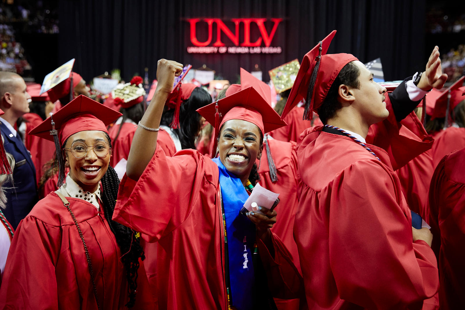 Students in their red caps and gowns at graduation.