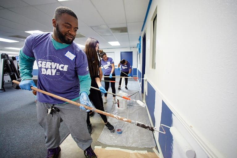 A student helps paint the Boys & Girls Club for Services Day