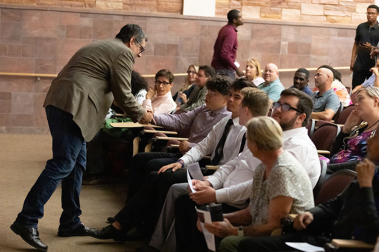 Faculty gather in a lecture hall