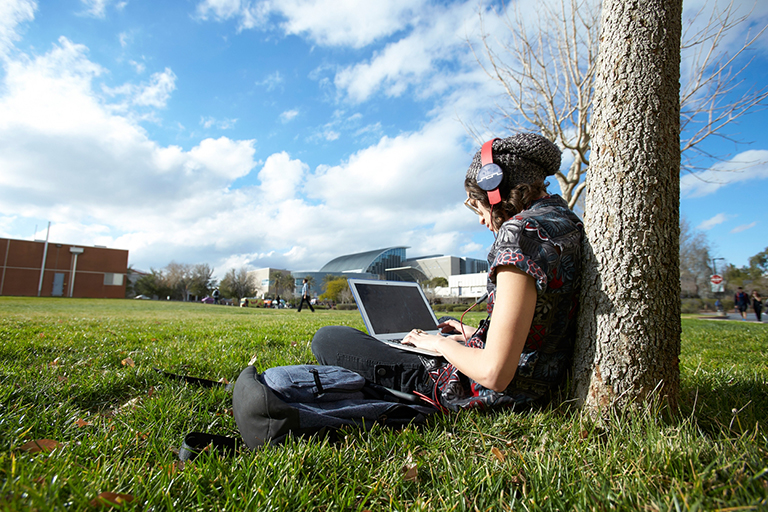 Student sitting under a tree.
